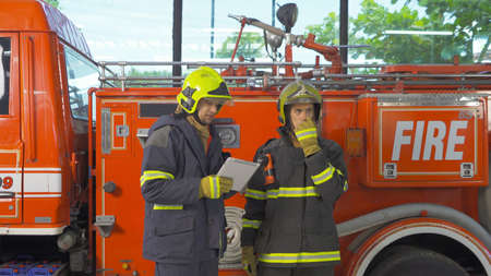A group of caucasian firefighters or firemen team with uniform and tablet device, working on their career. An emergency accident rescue. People. Hero teamwork with a fire truck car. Service job Banco de Imagens