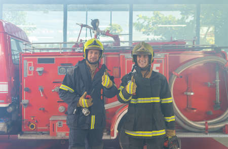 Portrait of a group of caucasian firefighters or firemen team with uniform, working on their career. An emergency accident rescue. People. Hero teamwork with a fire truck car. Service job