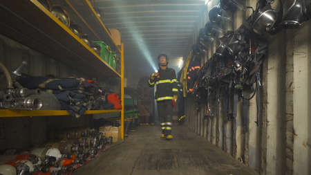 A caucasian firefighter or fireman with uniform inspecting in protection gear storage with safety helmet . An emergency accident rescue. People. Hero. Service job Banco de Imagens