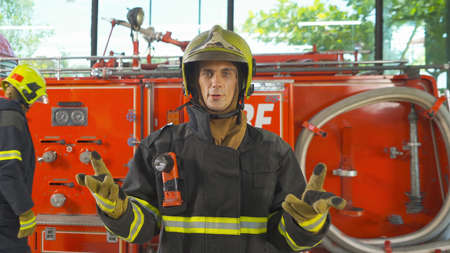 A Caucasian man firefighter or fireman with uniform talking to colleagues in webcam group video call conference online, An emergency accident rescue. People. Hero teamwork with fire truck car. Service