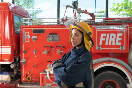 Portrait of a caucasian firefighter or fireman woman with uniform, working on their career. An emergency accident rescue. People. Hero with a fire truck or ambulance car. Service job