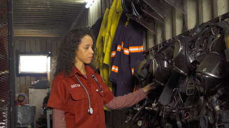 A caucasian first Aid doctor woman in uniform checking equipment safety and security at fire station gear storage, An emergency accident rescue. People. Service job Banco de Imagens