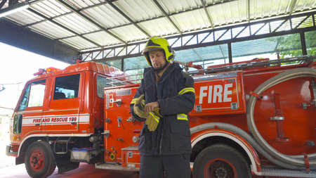 Portrait of a caucasian firefighter or fireman man with uniform, working on their career. An emergency accident rescue. People. Hero with a fire truck or ambulance car. Service job Banco de Imagens