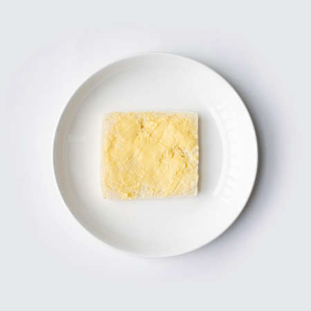 Butter on a slice of bread isolated on white background on a plate. Cooking breakfast. Wholewheat. Healthy food. Dairy product.