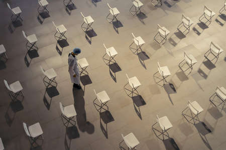 Top view of medical healthcare doctor with  empty chairs set at vaccination hub inside a hospital. Social distancing. COVID 19 pandemic. Vaccination hub. Art design pattern background. Coronavirus