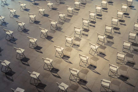 Top view of empty chairs set out for people to wait for vaccine dose inside the shopping mall. Social distancing. COVID 19 pandemic. Vaccination hub. Art design pattern background. Closed retail shop.