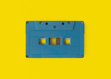 Top view of vintage audio tape cassette isolated on yellow background. 1980s recorder. Old pop music. album collection.