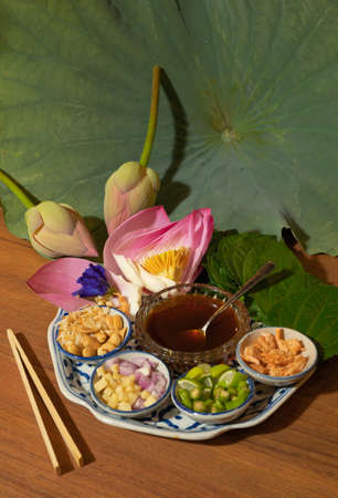 A set of Miang kham, Thai appetizer food with Lotus flower and leaf wrapped on traditional ceramic serving dish.