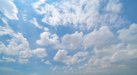 Clear blue sky with white fluffy clouds at noon. Day time. Abstract nature landscape background. 写真素材