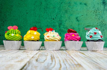 tortas de cumpleaños: Pastelitos de colores sobre un fondo de madera Foto de archivo