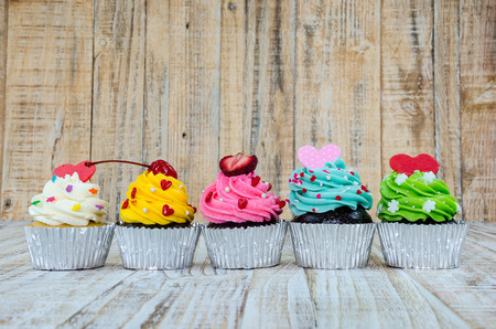 cupcakes: Colorful cupcakes on a wooden background