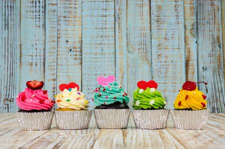 decoracion de pasteles: Pastelitos de colores sobre un fondo de madera Foto de archivo