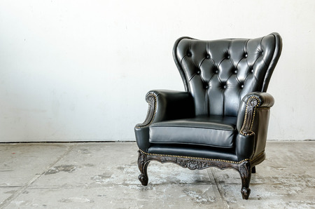 Black genuine leather classical style sofa in vintage room