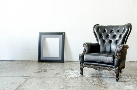 sitting on sofa: Black genuine leather classical style sofa in vintage room with frame