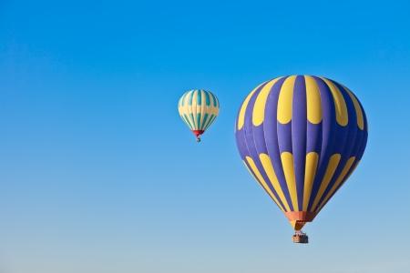 Hot air balloons drifting across a blue sky in Cappadocia,\ Turkey