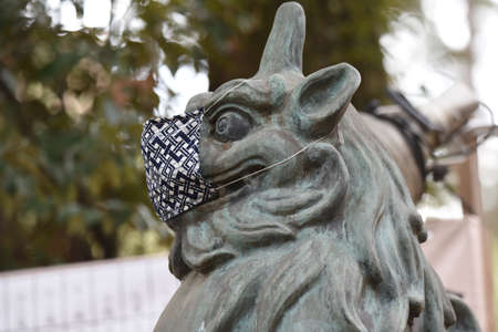A guardian dog of a shrine wearing a mask for preventing new corona infection. 写真素材