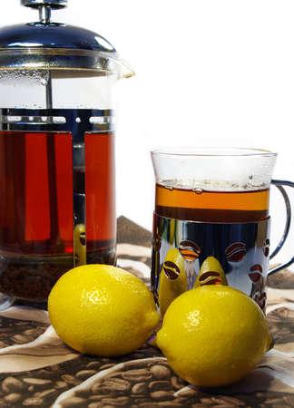 black tea whith lemon in the transparent mug and kettle  photo