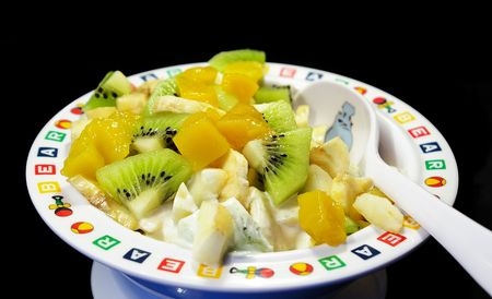 Fruit salad in a plate isolated on a black background photo