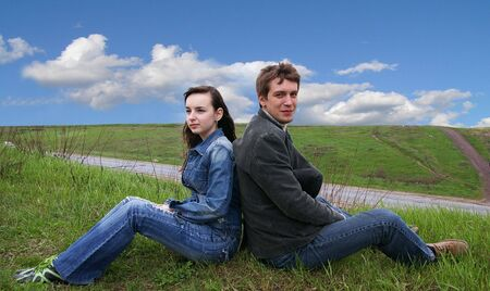 Guy and girl sits on a grass on a background of the sky photo