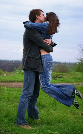 The guy kisses his girl on a background of the nature photo