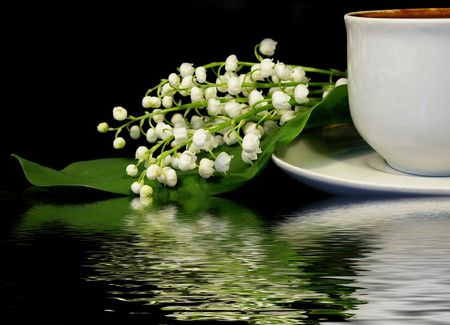 Flowers of a llies of the valley and white cup of black coffee on a black background Stock Photo - 2950651