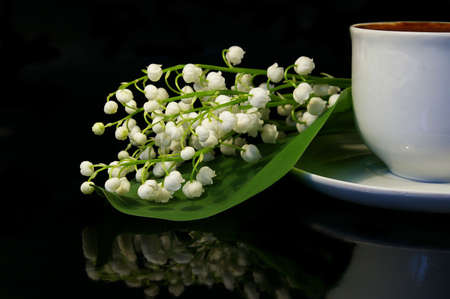 Flowers of a llies of the valley and white cup of black coffee on a black background Stock Photo - 2950649