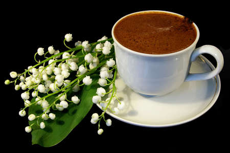 Flowers of a llies of the valley and white cup of black coffee on a black background Stock Photo - 2950656