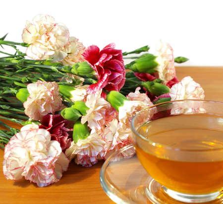 Cup of tea and bouquet of carnations isolated on a white background photo