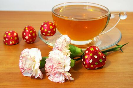 Cup of black tea, sweets and flowers Stock Photo