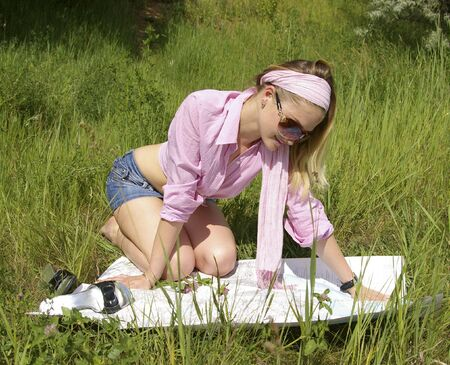 Beautiful girl looks at the map on nature photo