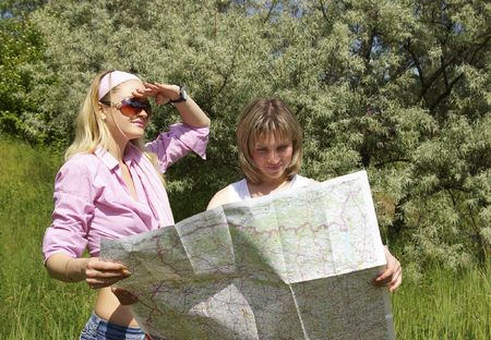Two beautiful girls look at the map on nature photo