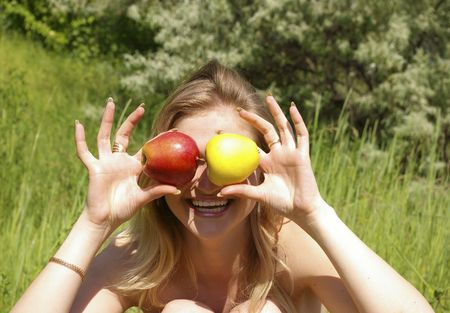 A young cute woman holding up two apples photo