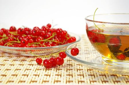 Red currant and herbal tea in a transparent cup photo