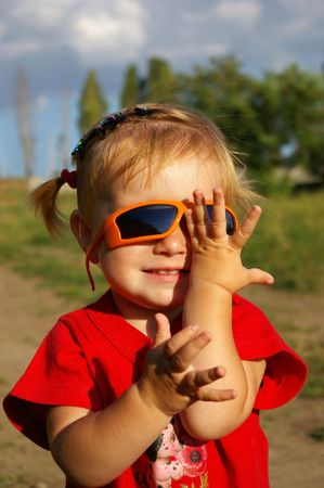 The little girl plays with glasses on a background of the nature photo
