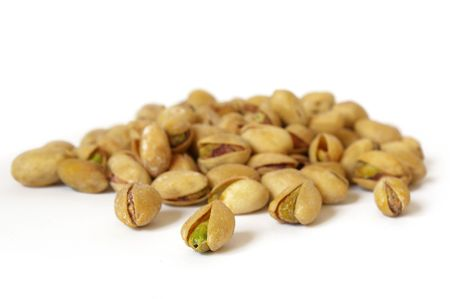 Heap of salty pistachios isolated. Soft focus photo