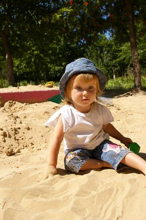 The girl plays sand on a garden photo