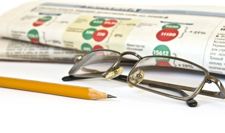 Newspaper and glasses isolated on white background photo