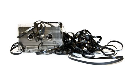 Old audio cassette with unwound tape on white photo