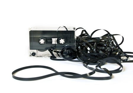 unwound: Old audio cassette with unwound tape on white