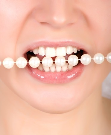 stodio: Woman open mouth and teeth biting on faux pearls