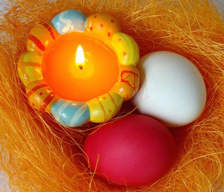 Eggs and candle in a small nest on white background photo
