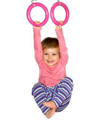 hangs: Cute girl hangs from rings on white background