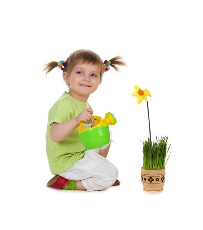Cute little girl watering the flower. Studio shot Stock Photo