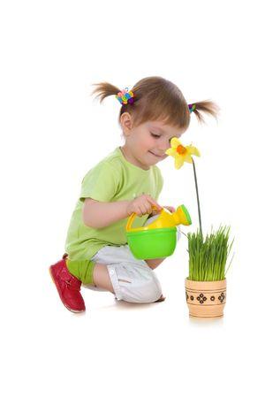 Cute niña regando la flor. Studio shot Foto de archivo