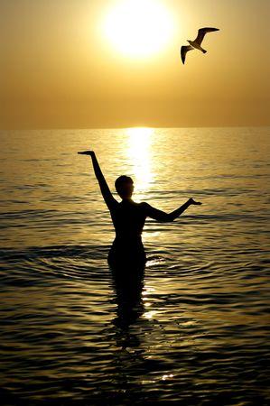 Young beatiful woman meditating in a sea  photo