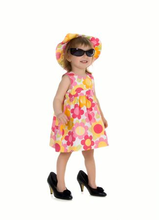 Little girl in big shoes. Isolated on white background Stock Photo