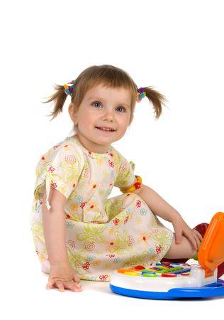 Cute little girl sit near toy laptop. Studio shot photo
