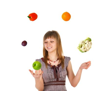 Woman juggling with fruits and vegetables. Isolated on white background photo