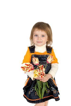 pinafore: Cute little girl giving tulips. Studio shot Stock Photo