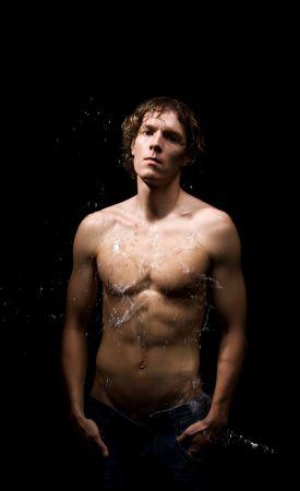 Wet beautiful man. Studio shot. Black background photo